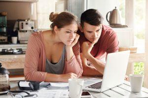 pareja concentrada en calcular el contenido del seguro de hogar