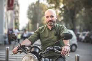 Imagen de un adulto con un buen seguro de moto, que posa con su motocicleta